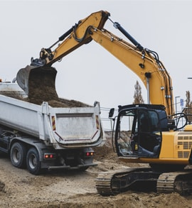 Tiefbau in einer Grube: Bagger und LKW in der Zusammenarbeit.