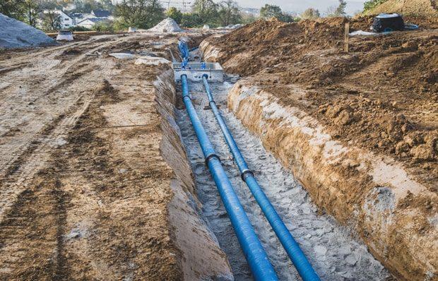Auf Sand gebettete Wasserleitungen in einem Graben.